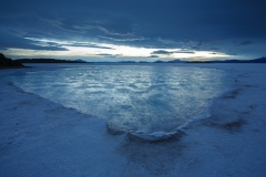 Post sunset sky reflected in brine pools on the Salar