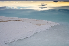 Salt shoreline and sunset sky reflected in brine pools on the Salar